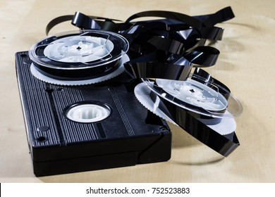 Image on video tape. Videotape tape wound on spools. Wooden table, black background.