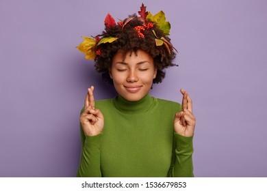 Image of optimistic luck woman crosses finger for good luck or fortune, anticipates for miracle, wears green poloneck, keeps eyes closed, hopes for good autumn weather to have walk in fall park