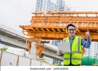 Image outside the industrial construction engineers in yellow protective ear muff discuss new project while using laptop and happy smile on the open building site near the crane.