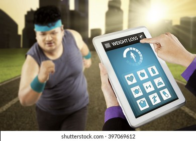 Image of overweight man running on the field with weight loss application on the digital tablet screen