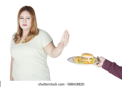 Image of overweight woman refusing burger on a plate while standing in the studio