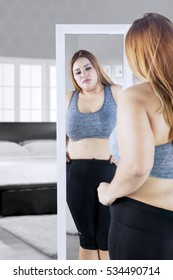 Image of overweight young woman looking at the mirror while touching her belly in the bedroom