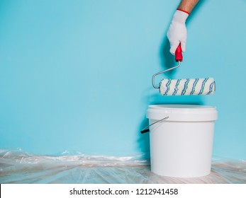 Image of paint can and man holding paint roller in front of blue wall.