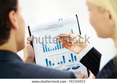 Image of paper being discussed by two business partners