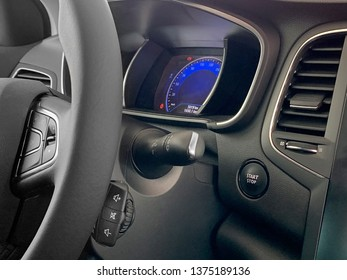 image of part of the car steering wheel with shift paddles and dashboard close up