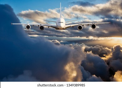 Image of a passenger plane flying above the sunset clouds. Front view of the aircraft. The aircraft is located at the top of the image. Most of the image is vacant for your text.