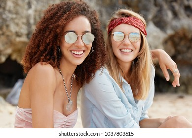 Image of passionate homosexual couple embrace, wear trendy sunglasses. Beautiful dark skinned young female hugs her female partner, looks at sunshine, sit together. Happy moment. Samesex relations