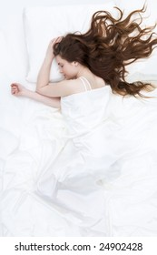 Image of peaceful girl lying on linen bed under satin cloth and dreaming