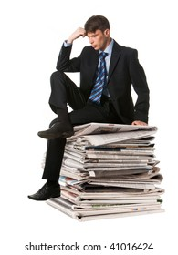 Image of pensive businessman sitting on the stack of newspapers