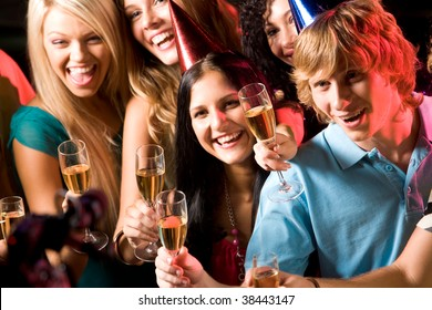 Image of people with hats holding glasses of champagne