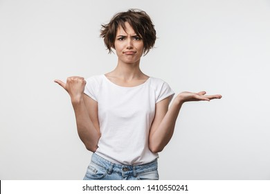 Image of perplexed woman with short hair in basic t-shirt pointing finger aside at copyspace isolated over white background