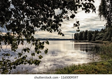 The image of the pipe of the power plant reflects on the surface of a lake at Haapavesi, Finland. The summer morning sun rises in the background.