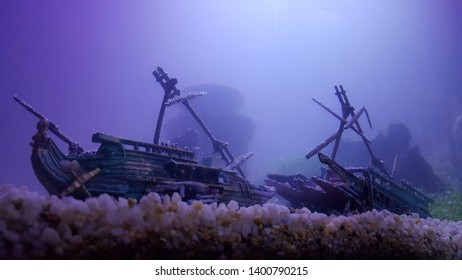 The image of a pirate ship submerged with a dark atmosphere, with mountains and trees under the water from the top that crashed. Submerged materials create a mysterious and frightening sight that will