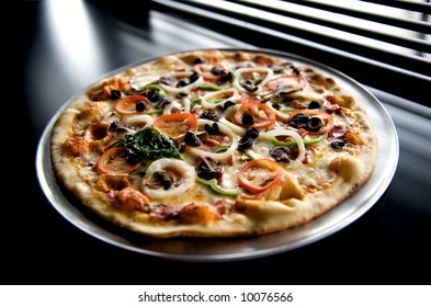 Image of pizza with sliced vegetable topping