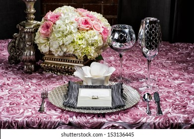 Image of a place setting at a wedding on pink