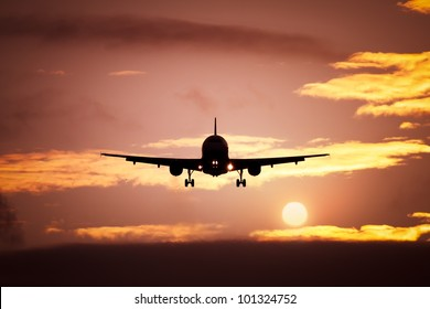 An image of a plane in the sunset sky