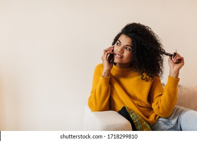 Image of pleased african american woman talking on cellphone while sitting on couch in living room