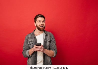 Image of Pleased bearded man holding smartphone and looking away over red background