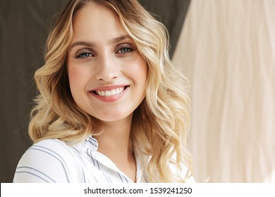 Image of pleased elegant blonde woman smiling at camera standing isolated over fabric background