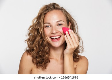 Image of pleased half-naked woman laughing and using facial sponge isolated over white background