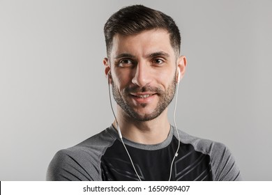Image of pleased unshaven sportsman using earphones and smiling isolated over gray background