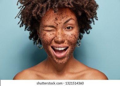 Image of pleased young curly woman blinks eye, has positive expression, applies black coffee mask, does peeling of skin, poses with bare shoulder, isolated over blue background, visits spa salon
