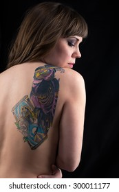 Image of plump woman with tattoo owl, from back on black background