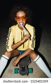 Image of positive african american girl in streetwear eating long jelly candy and sitting on skateboard at night outdoors