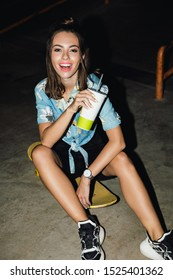 Image of positive brunette girl in streetwear drinking soda and sitting on skateboard at night outdoors