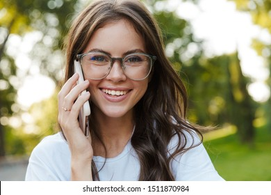 Image of a positive happy young cheery student lady outdoors in nature green park talking by mobile phone.