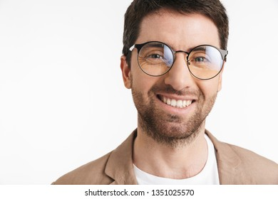 Image of positive man 30s with stubble wearing jacket and eyeglasses smiling on camera isolated over white background
