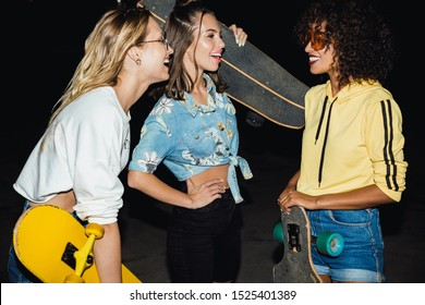 Image of positive multiethnic girls in streetwear smiling and holding skateboards at night outdoors