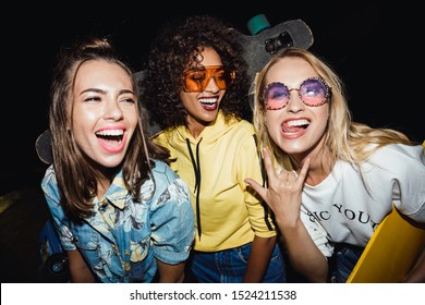 Image of positive multinational girls in streetwear smiling and holding skateboards at night walk outdoors