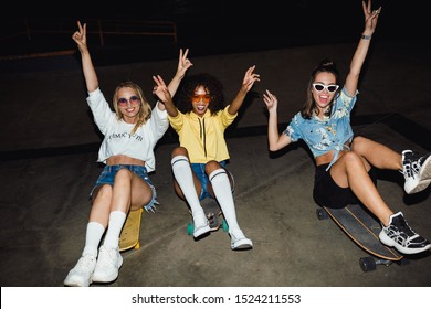 Image of positive multinational girls in streetwear smiling and riding on skateboards at night party outdoors