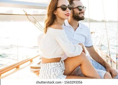 Image of a positive optimistic happy young loving couple outdoors on yacht in sea hugging.