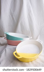 Image of Pottery, green turquoise yellow and pink pastel ceramic bowl on the white cloth or vintage white look fabric background