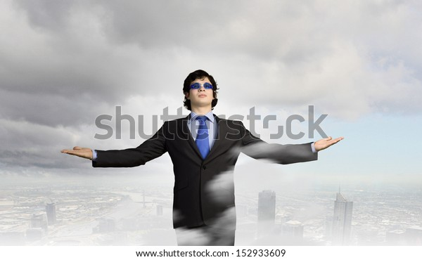 Image of powerful businessman standing against urban scenics