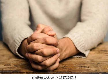Image of praying hands. Praying hands of young man on a wooden desk