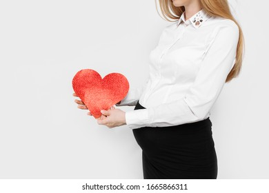 Image of pregnant business lady hugging her belly, holding red heart near her belly, on white background