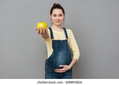 Image of pregnant cheerful woman with apple in hand standing isolated over grey wall. Looking at camera.