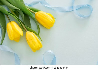 Image of presents with yellow tulips and blue ribbon