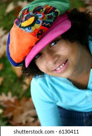 image of a pretty biracial girl in a funky hat....outdoor setting