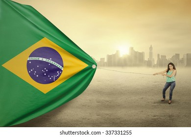 Image of pretty brazilian woman with casual clothes pulling a flag of Brazil