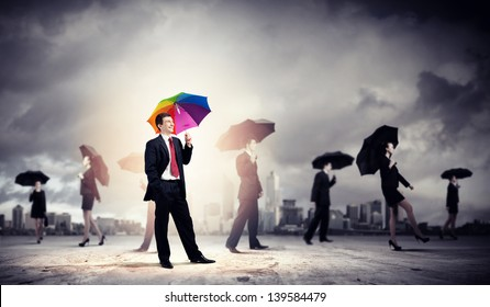 Image of pretty businessman with umbrella walking in crowd of people