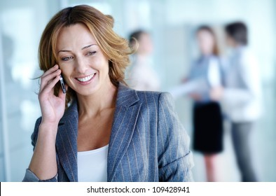 Image of pretty businesswoman calling on the phone in working environment