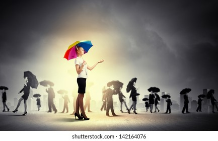 Image of pretty businesswoman with umbrella walking in crowd of people