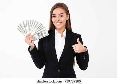 Image of pretty cheerful business woman standing isolated over white background showing thumbs up holding money. Looking camera.