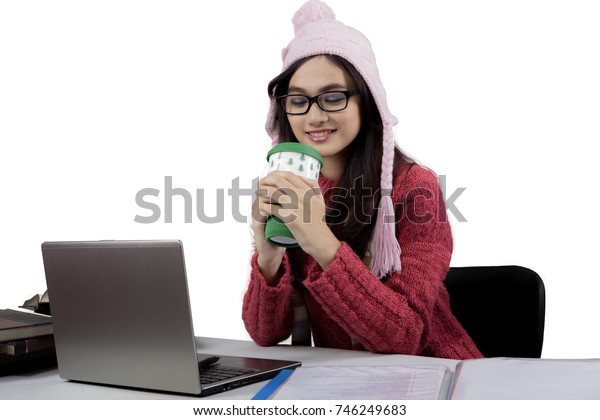 Image of a pretty female college student wearing winter clothes while studying with a laptop and enjoying hot chocolate