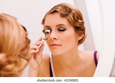 Image of pretty female looking in mirror while curling her eyelashes