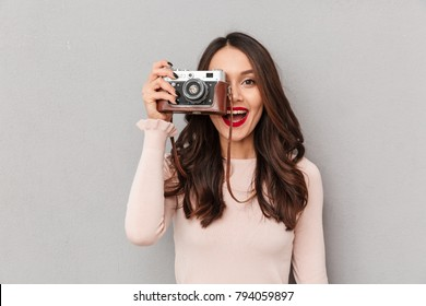 Image of pretty female photographer holding retro camera doing favorite shots isolated, against gray background copy space
